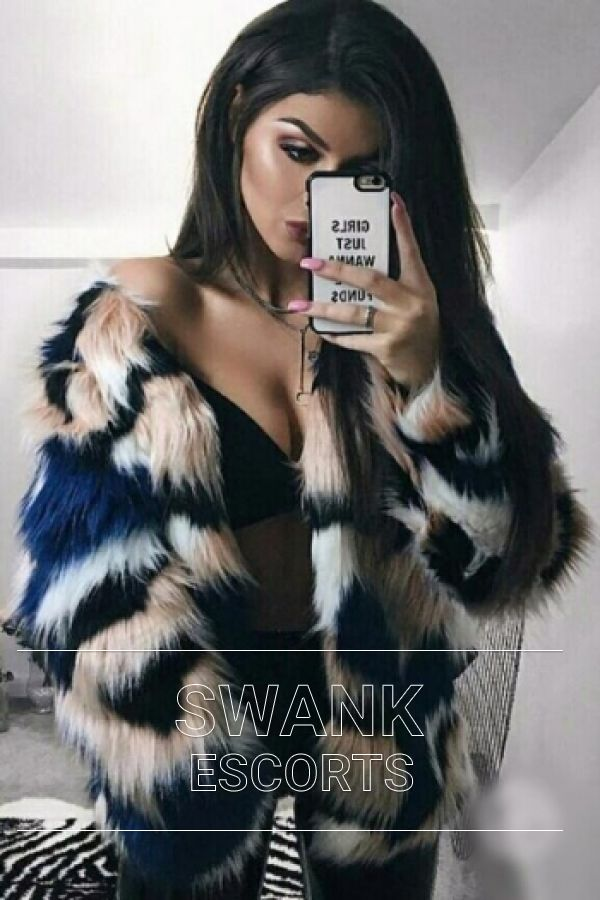 Cara wearing black and white coloured fur coat and black lingerie looking sexy taking mirror selfie
