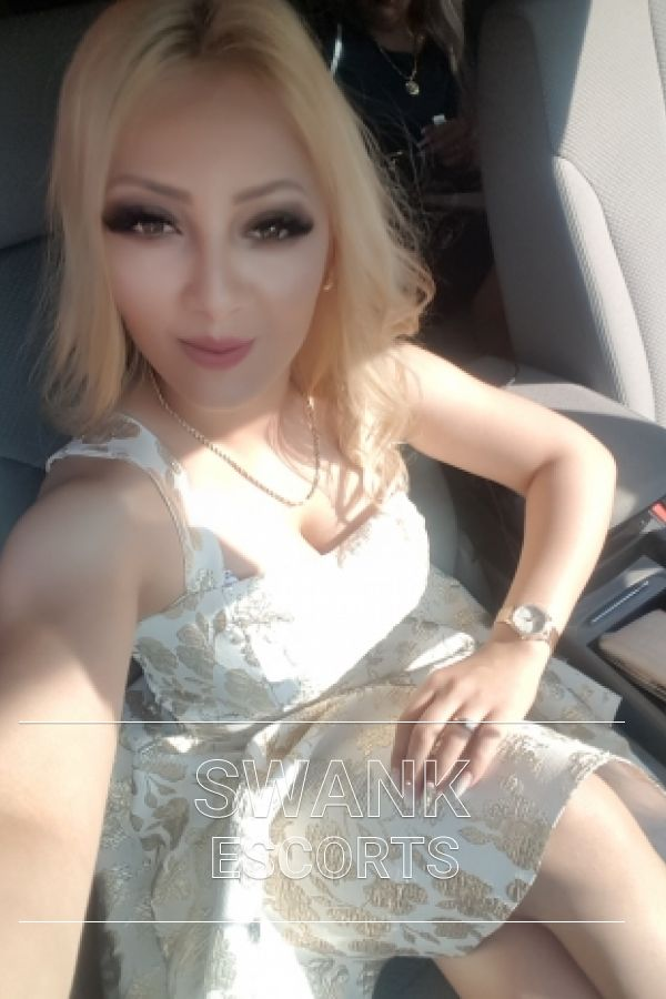 Maya taking a selfie in car wearing nice white dress