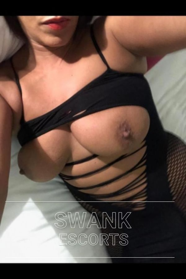 Leah showing off bust in selfie while leaning back on the bed in black lingerie