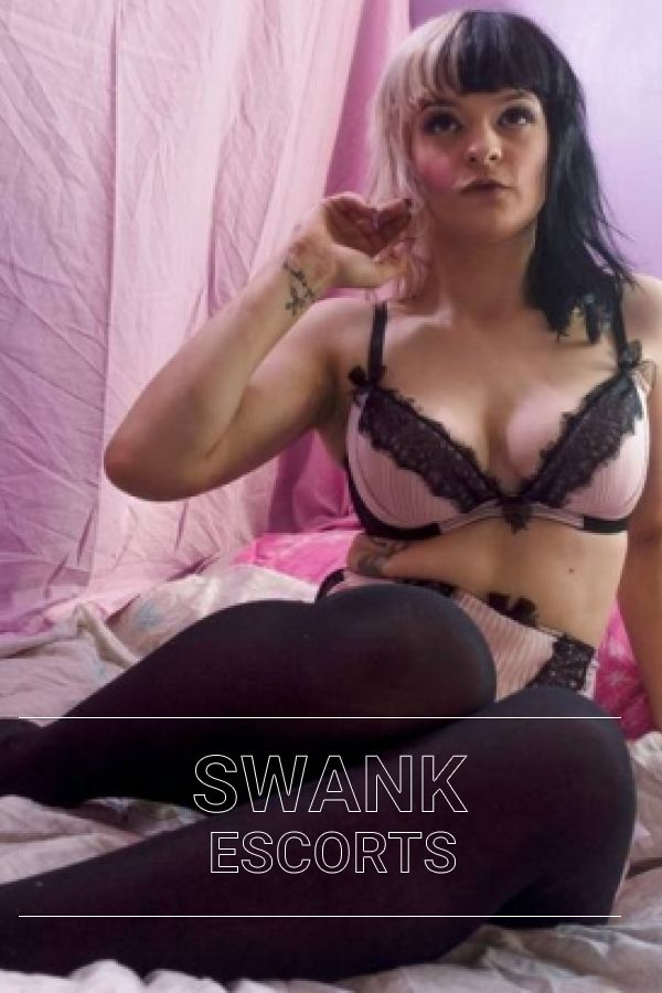 Bambii in black tights and pink and black lingerie posing in bed